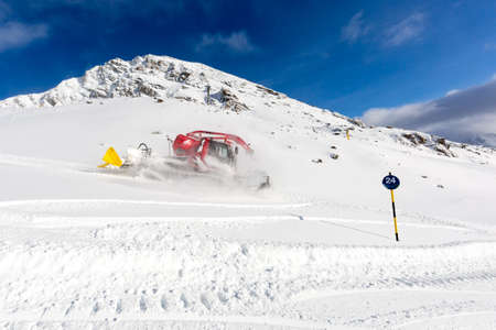 snow grooming machine: Piste machine grooming ski tracks with fresh snow at ski resort in the Alps.