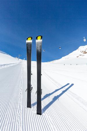 groomed: Pair of modern carving skis standing on newly groomed ski piste.