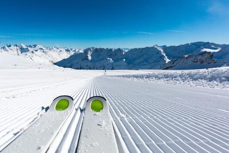 Coppia di sci nuovi in ??piedi sulla neve fresca sulla pista da sci appena preparate a stazione sciistica in una giornata invernale di sole.