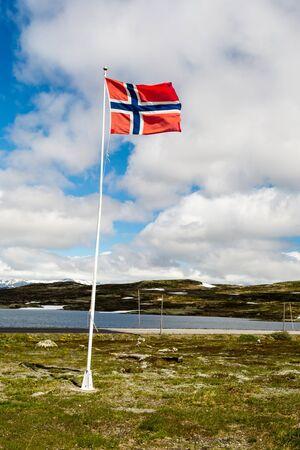 flagpoles: Norwegian flag on flagpole near the famous Hardangervidda plateau in western part of Norway. Stock Photo