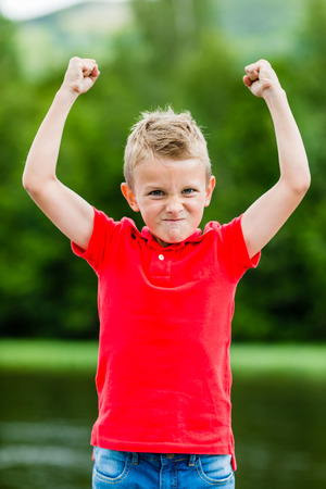 Boy with raised arms and fists showing his excitement for recent success and high self esteem.