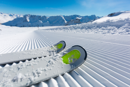 snow ski: Pair of ski tips standing on the fresh snow on newly groomed  ski piste at ski resort on a sunny winter day. Stock Photo