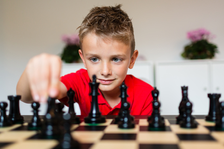 game play: Young white child playing a game of chess on large chess board.