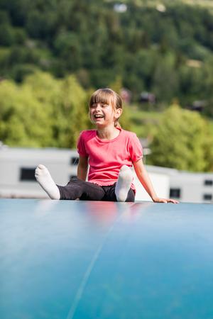 scandinavian girl: Young Scandinavian girl playing and having fun while sitting on inflatable bouncing pillow.