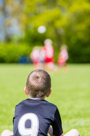 mates: Young boy watching his team mates play a kids soccer match on soccer field with green grass.