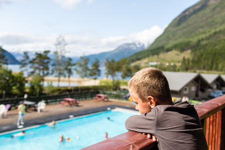 hardangerfjord: Young boy overlooking the swimming pool area at summer holiday resort at Kinsarvik near Hardangerfjord in Norway. Stock Photo