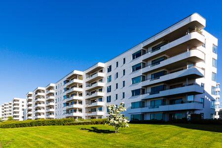 blanco edificio residencial contemporáneo contra un cielo azul. Ideal para la ilustración de bienes raíces o conceptos de inversión.