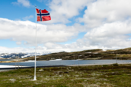 flagpole: Norwegian flag on flagpole near the famous Hardangervidda plateau in western part of Norway. Stock Photo