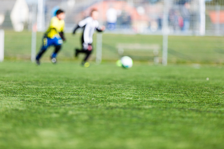 soccer pitch: Blur of young boys playing a kids soccer match outdoors on an green soccer pitch. Stock Photo