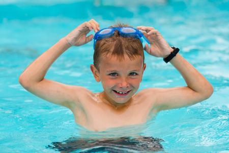 nadar: El muchacho joven con gafas de nataci�n que se divierten en la piscina en un d�a nublado.