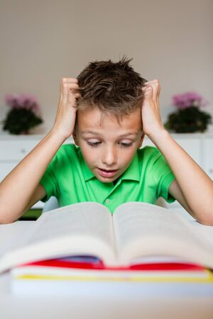 textbook: Young boy in green polo shirt having serious learning difficulties while trying to read a textbook from school.