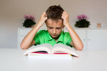 assignments: Young boy in green polo shirt having challenges reading a text in a school book.