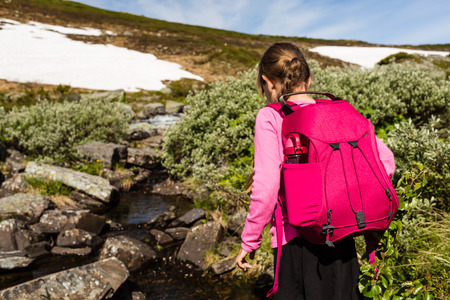 scandinavian girl: Scandinavian girl hiking outdoors in the nature in Norway wearing a blue backpack and exploring the wilderness on a sunny day.