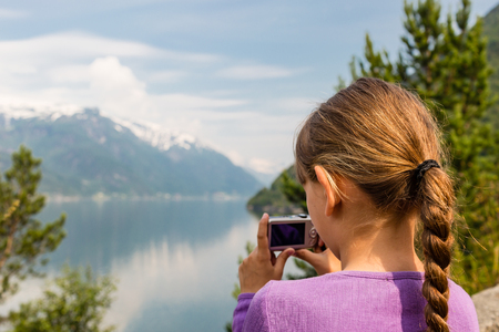hardangerfjord: Young girl in Norway taking a picture of the surrounding scenery with her compact digital camera. Stock Photo