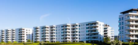 Moderne weiße Wohngebäude gegen einen blauen Himmel. Ideal für Darstellung von Immobilien oder Anlagekonzepten.