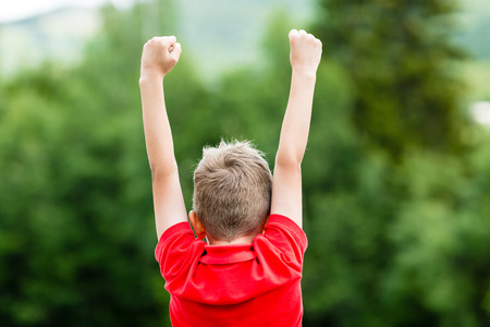 raised arms: Child with raised arms celebrating his success or victory while standing outdoors.