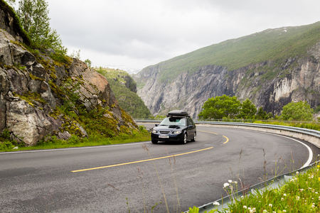 Car driving on the Riksvei 7 public road crossing the large Hardangervidda plateau in Western Norway.