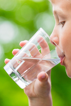 scandinavian people: Close-up of young scandinavian child drinking fresh and pure tap water from glass with a blurred green background. Stock Photo