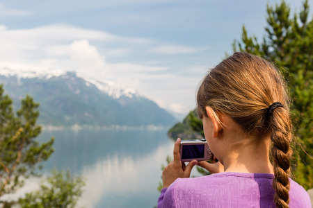 Young girl in Norway taking a picture of the surrounding scenery with her compact digital camera. Stock Photo