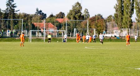 Ondiepe scherptediepte schot van groep mannelijke voetballers spelen amateur voetbalwedstrijd op zonnige zomerdag op eenvoudige sport-locatie in Denemarken.