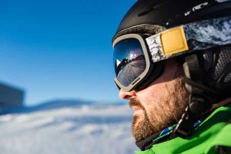 ski goggles: Close-up of male skier with large oversized ski goggles standing on the top of a mountain ready for skiing.