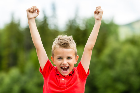 Boy with raised arms and fists showing his excitement for recent success and high self esteem. Imagens