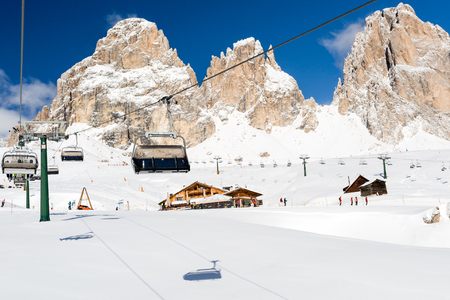 chair on the lift: Chair lift and ski slope near the popular ski resort Canazei in the Dolomites in Italy.
