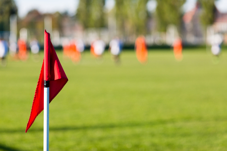 field depth: Shallow depth of field shot of group of male soccer players playing amateur soccer match on sunny summer day on simple sports venue in Denmark.