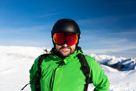 Close-up of happy male skier with large oversized ski goggles standing on the top of a mountain ready for skiing. Stock Photo