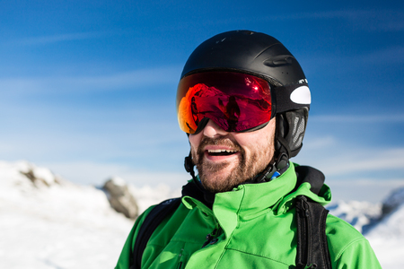 ski goggles: Close-up of happy male skier with large oversized ski goggles standing on the top of a mountain ready for skiing. Stock Photo