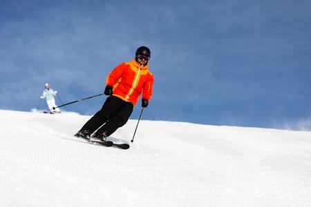 Sciatore maschio in arancione sci giacca da sci giù una stazione funzionare alla stazione sciistica in una giornata di sole invernale.