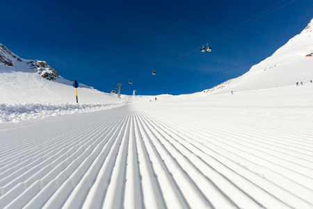 Fresh snow at recently groomed ski run at ski resort in the Alps on a sunny winter day. Stock Photo
