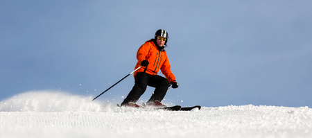 Male skier in orange ski jacket skiing down a ski run at ski resort on a sunny winter day.