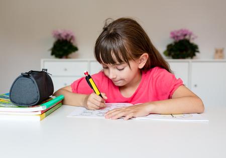 Jeune fille blanche écrit avec son crayon et de faire son élémentaire devoirs scolaires tout en étant assis à table blanche.