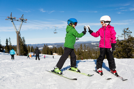 Two kids doing high five while standing on ski slope at the ski resort Trysil in Norway. Stock Photo