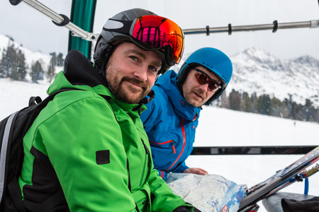 skiers: Close-up of happy male skiers in a modern gondola ski lift.