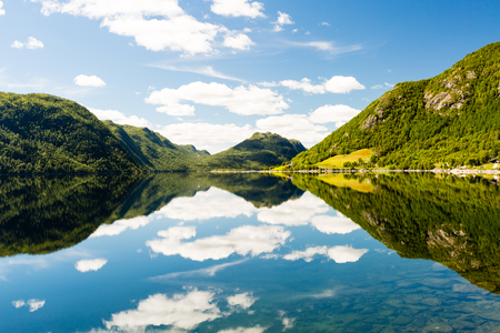 Reflection of skies and light on a calm lake in western Norway on sunny summer day with mountains in the background. Stock Photo