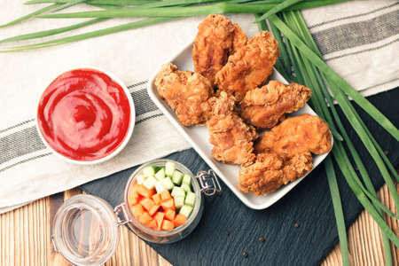 Parts of chicken wings in breading with tomato sauce and green onion on black shale plate and brown wooden table Stock Photo
