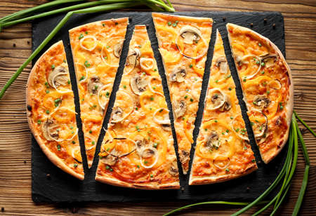 Slised vegeterian home made pizza with yellow pepper and mushrooms, onion, tomatoes. Top view on wooden table