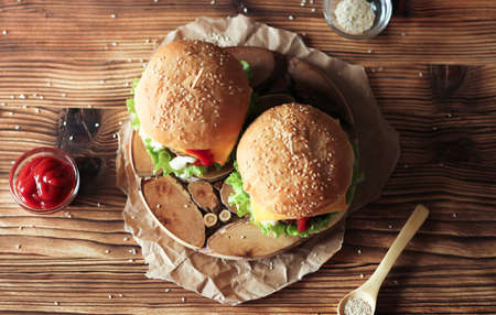 Two handmade burgers with beef, salad and cheese on wooden brown table. Buns with sesame seeds Stok Fotoğraf