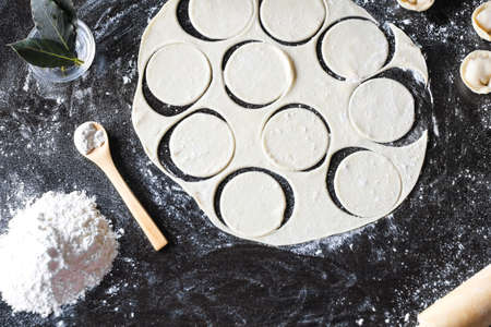 Preparation of pelmeni. Top view. The Ingredients on a black table. Traditional Russian cuisine