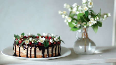 Drip cake with chocolate, decorated with strawberries, jasmine flowers and honeysuckle on white wooden table on big plate Foto de archivo