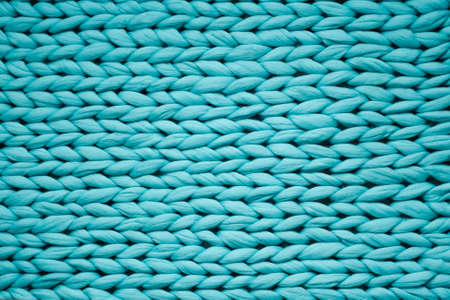 Texture of blue big knit blanket. Large knitting. Plaid merino wool. Top view