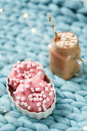 Pink donut with marshmallow and hot chocolate in cup on blue merino knit blanket.