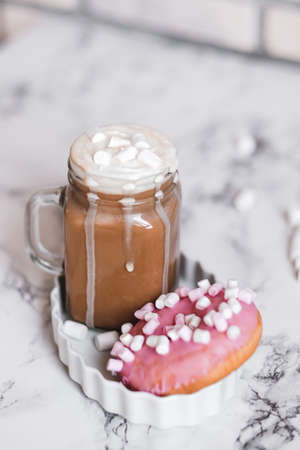 Pink donut with marshmallow and hot chocolate in glass cup on table.