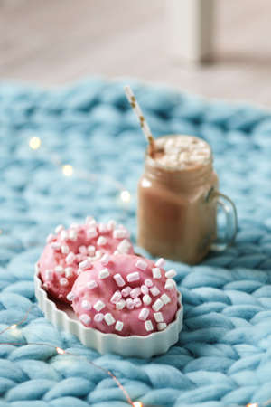 Pink donut with marshmallow and hot chocolate in cup on blue merino knit blanket