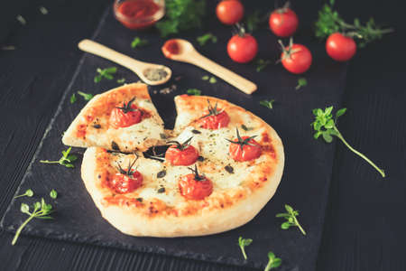 Margherita home made pizza with basil on dark table. Foto de archivo