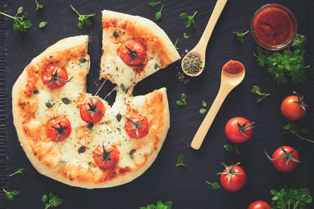 Margherita home made pizza with basil. Top view on dark table.