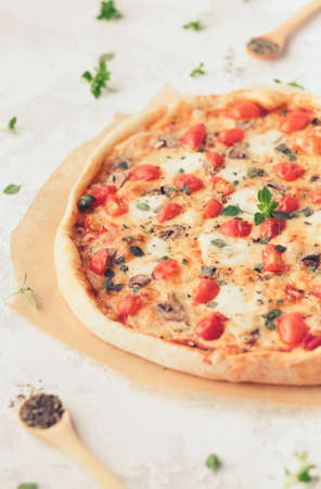 Margherita home made pizza with basil and mushrooms. Top view on white table.