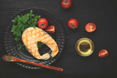 Grilled salmon with lemon and basil on dark background. Black plate